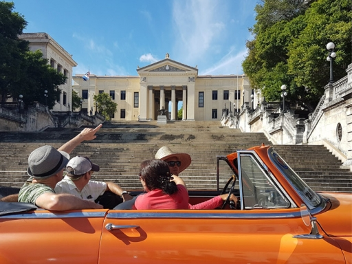 Driving past the University of Havana in a convertible classic car.